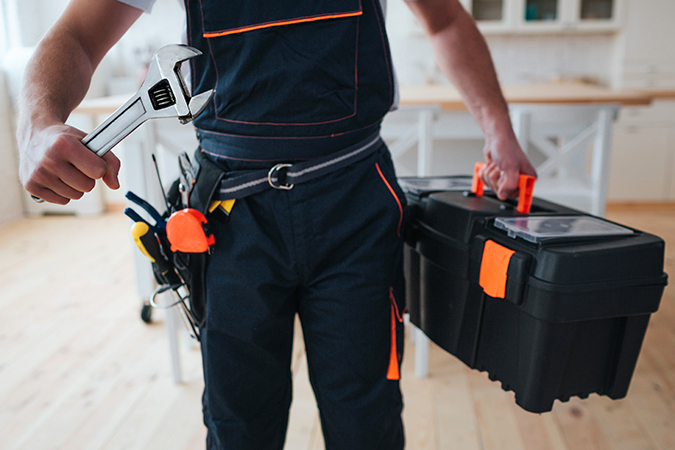 Cut view of handyman holding tool box and wrench in hands. He stand in kitchen. Guy wear special uniform. Daylight.